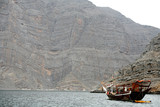 dhow by cliff, musandam peninsula oman poster