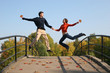 jump couple on autumn bridge