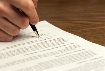 man signs document