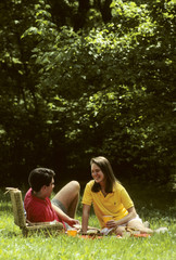 young couple have picnic in park