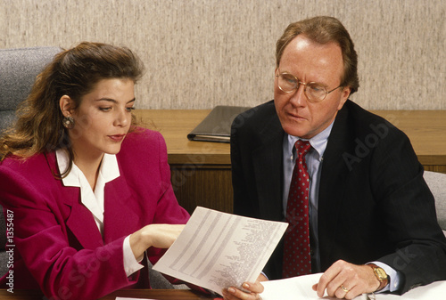 man and woman discuss project in office