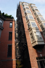 tall building with fire escape and bay windows full color