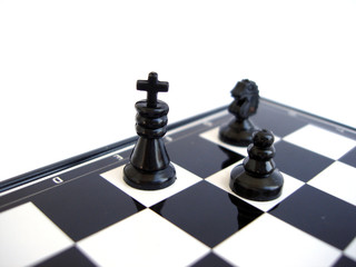 black chess king stands with figure on a chess board