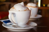 two cappuccino cups with milk foam