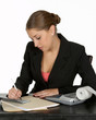 business woman in black suit writing check at desk
