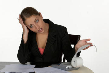 perplexed young business woman at calculator