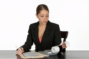 business woman balancing checkbook at desk
