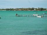 femme qui pêche sur lagon turquoise et ponton poster
