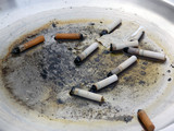 cigarette butts in dirty metal ashtray poster