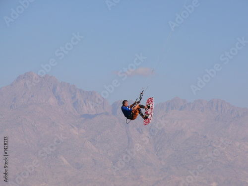 kitesurfer above mountains