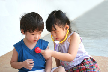 girl & boy playing with stethoscope
