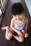 girl playing stethoscope on toy puppy