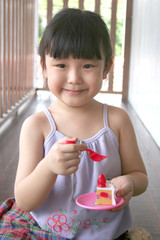 girl playing toy cake