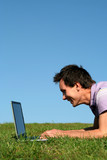 man lying on the grass using laptop poster