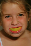 little girl smiling with orange peel poster