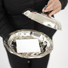 woman showing a business card on a silver plate