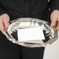 woman showing a blanco  card on a silver plate