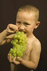 little boy with grape on black background