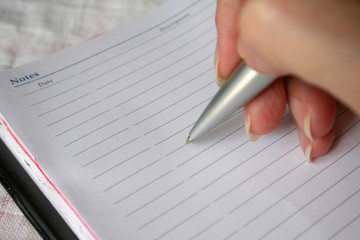 hand holding a pen writing on note book