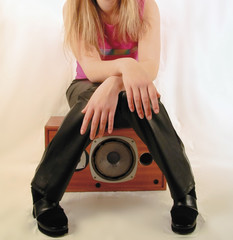 young girl sitting on speaker