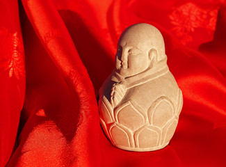 chinese stone buddha sculpture on red silk