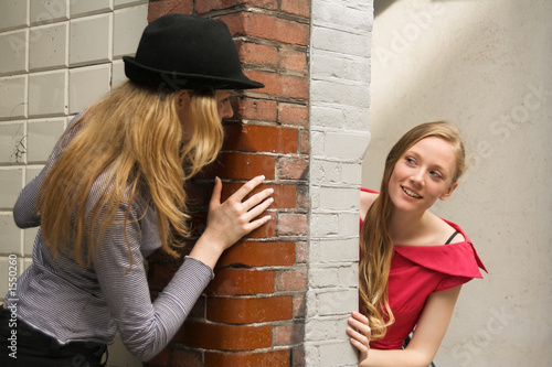 two girls peeking around the wall