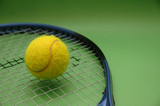 tennis ball and racket on green background