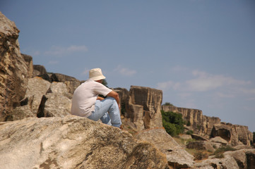 man sitting at the top of rock