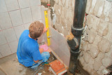plumber placing tiles poster