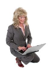 business woman kneeling working on laptop