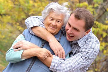 young man hugs elderly woman
