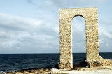 ancient arch - ruins over seashore, front view poster