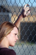 teen girl looking through fence
