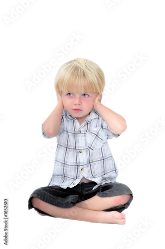 young boy with his hands over his ears and white background