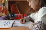 young girl doing homework poster
