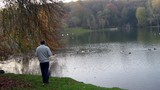 man stands alone beside lake.evening.autumn poster