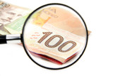 magnifying a 100 canadian dollar poster