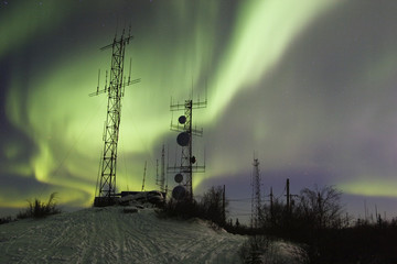 scientific antennas under night sky with northern