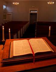 bible on pulpit with candles - vertical