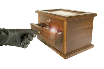hand in black glove opening casket with jewelry