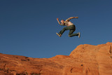 tattooed man jumping on the rocks