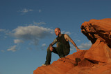 tattooed man sitting on the red rocks poster