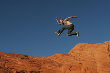 tattooed man jumping on the rocks