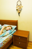 girl sleeping in bed with dreamcatcher above poster