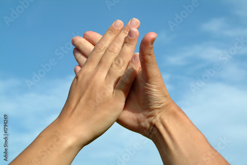 hands in hands against sky, gesture of friendship concept