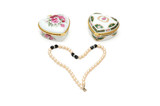two heart shaped boxes and beads isolated on white