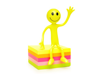 smilies sitting on a stack of coloured papers