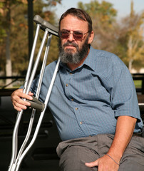 older gentleman holding crutches