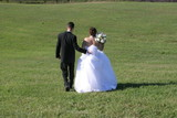 bride and groom walking with green grass poster