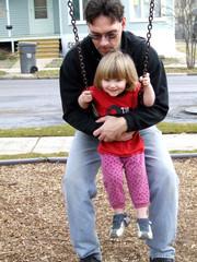 man holding baby on swing